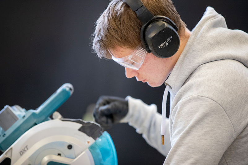 Male apprentice with cutting saw