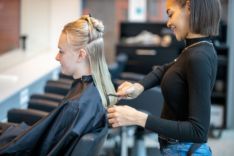 Female apprentice cuts hair on customer